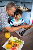 Grandfather assisting grandson using laptop. In kitchen at home Royalty Free Stock Images