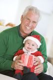 Grandfather With Baby In Santa Outfit Royalty Free Stock Image