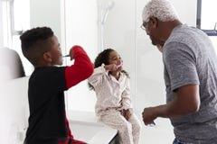 Grandfather In Bathroom Wearing Pajamas Brushing Teeth With Grandchildren stock image