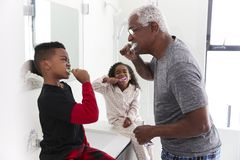 Grandfather In Bathroom Wearing Pajamas Brushing Teeth With Grandchildren stock images