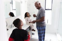 Grandfather In Bathroom Wearing Pajamas Brushing Teeth With Grandchildren stock photography