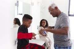 Grandfather In Bathroom Wearing Pajamas Helping Grandchildren To Brush Teeth stock photo