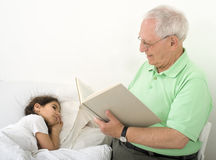 Grandfather bed time story. Grandfather reading to grandchild a bed time story Stock Images