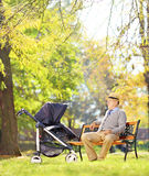 Grandfather on bench looking at his nephew in a stroller, in a p. Grandfather sitting on a bench and looking at his baby nephew in a stroller, in a park, shot Royalty Free Stock Photography