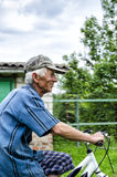 The grandfather on a bicycle. Fitness aged grandfather riding a bicycle through the countryside Stock Image