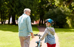 Grandfather and boy with bicycle at summer park Stock Images