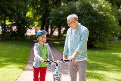 Grandfather and boy with bicycle at summer park Stock Photography