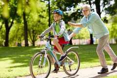 Grandfather and boy with bicycle at summer park Royalty Free Stock Photos