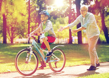 Grandfather and boy with bicycle at summer park Stock Image