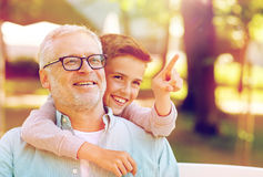 Grandfather and boy pointing finger at summer park Royalty Free Stock Photos