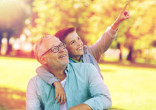 Grandfather and boy pointing finger at summer park Stock Image