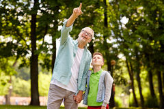 Grandfather and boy pointing up at summer park Royalty Free Stock Photo
