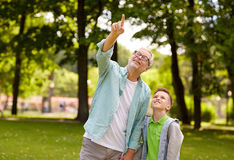 Grandfather and boy pointing up at summer park Royalty Free Stock Photos