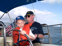 Grandfather and Boy Sailing. A young boy at the helm of a sailboat watched closely by his grandfather Stock Photos