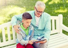 Grandfather and boy with tablet pc at summer park royalty free stock image
