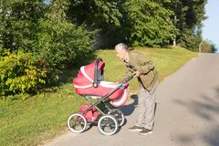 Grandfather carries granddaughter in baby carriager at sunset. stock photography