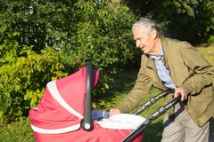 Grandfather carries granddaughter in baby carriager at sunset. Outdoor in the country stock photo