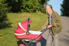 Grandfather carries granddaughter in pink baby carriager at sunset. royalty free stock photography
