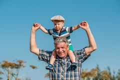 Grandfather carries grandson toddler boy on his shoulders. Child having piggyback ride on his grandfather`s back outdoors Royalty Free Stock Photo