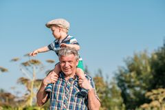 Grandfather carries grandson toddler boy on his shoulders Stock Photo