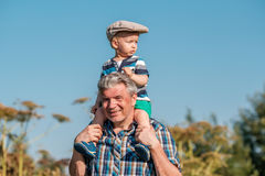 Grandfather carries grandson toddler boy on his shoulders Royalty Free Stock Images