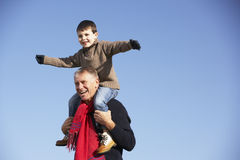 Grandfather Carrying Grandson Stock Images