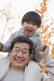 Grandfather Carrying Grandson on His Shoulders Royalty Free Stock Photography