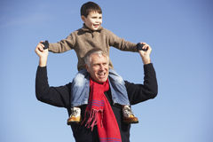 Grandfather Carrying Grandson On His Shoulders Stock Photo
