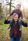 Grandfather Carrying Grandson On Shoulders During Walk Stock Photos