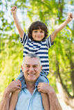 Grandfather carrying son on shoulders at park Royalty Free Stock Photography