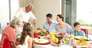 Grandfather carving chicken at dinner table for his family Stock Photography