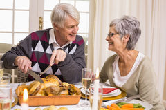 Grandfather carving roast turkey at christmas dinner Stock Images