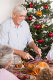 Grandfather carving turkey at christmas. Dinner Royalty Free Stock Images