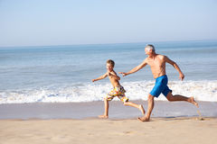 Grandfather chasing young boy on beach. In the sun royalty free stock images