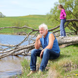 Grandfather and cheerful  granddaughter. Thoughtful grandfather and cheerful  granddaughter enjoy nature Royalty Free Stock Photos
