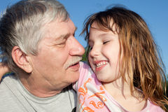 Grandfather and child. Portrait of a happy little girl and her grandfather Stock Image