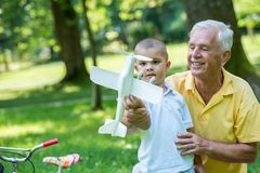 Grandfather and child have fun  in park Stock Photos