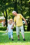 Grandfather and child have fun  in park Royalty Free Stock Photography