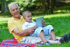 Grandfather and child in park using tablet Stock Image