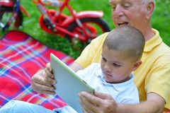 Grandfather and child in park using tablet Stock Photo