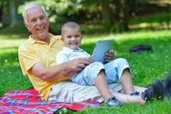 Grandfather and child in park using tablet Stock Photos