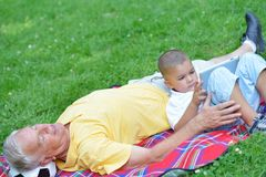 Grandfather and child in park using tablet Royalty Free Stock Photo