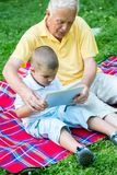 Grandfather and child in park using tablet Stock Photography