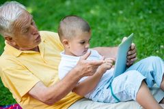 Grandfather and child in park using tablet Royalty Free Stock Image