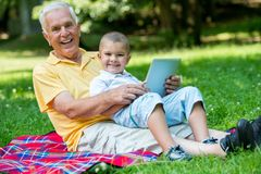 Grandfather and child in park using tablet Royalty Free Stock Photography