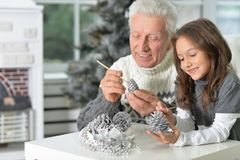 Grandfather with child preparing for Christmas. Portrait of grandfather with child girl preparing for Christmas together Stock Images