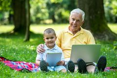 Grandfather and child using laptop Stock Image