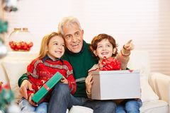 Grandfather with children and gifts at christmas. On the sofa royalty free stock image