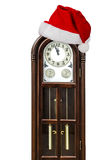 Grandfather clock and cap of Santa Claus, isolated on white back Stock Photo