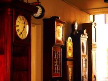 Grandfather clocks. Row of grandfather clocks against a passageway. Vintage feel and slight sepia Stock Image